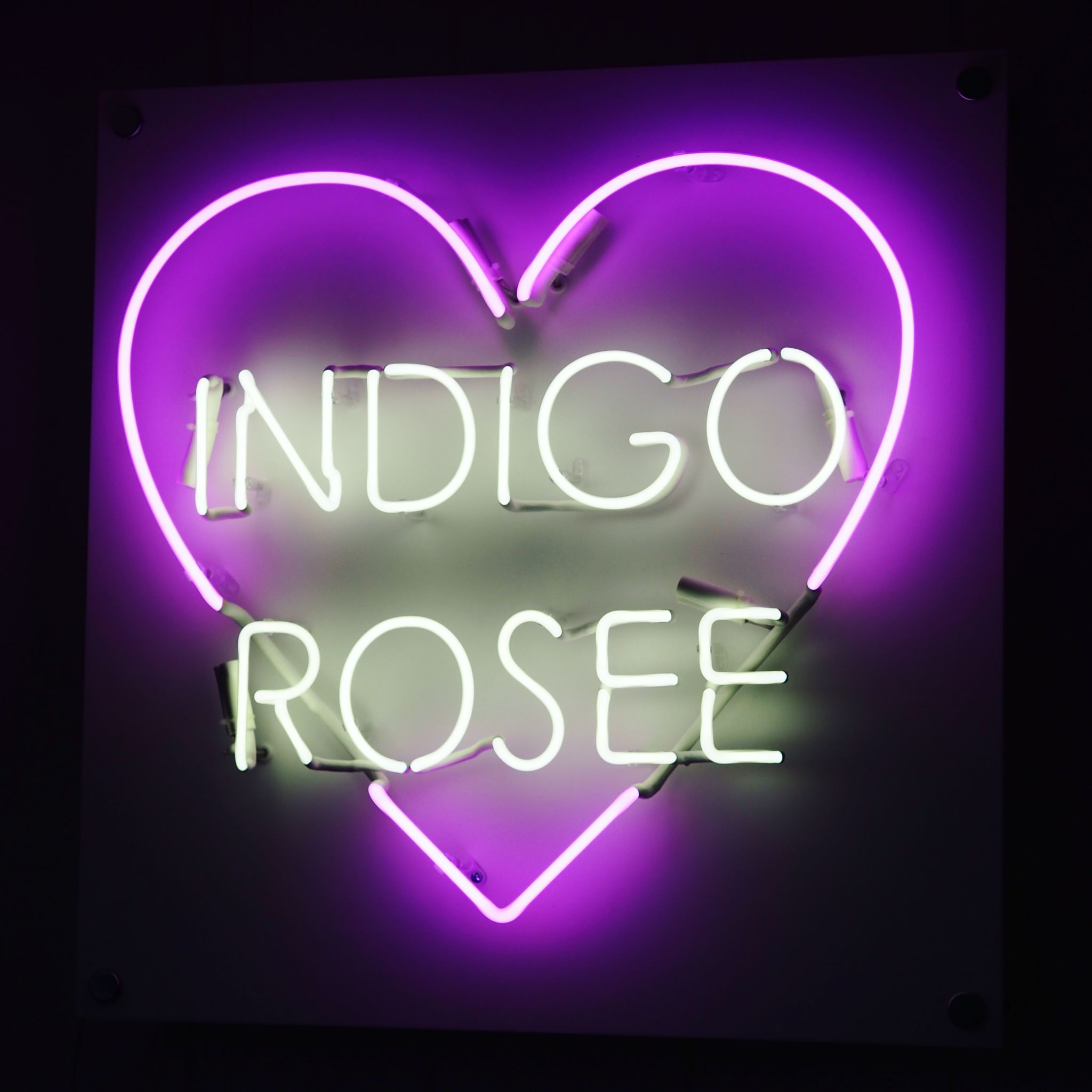 purple neon sign in the entrance to the office